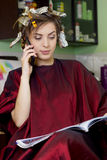 Business woman in hair dressing salon speaks on  phone Royalty Free Stock Image