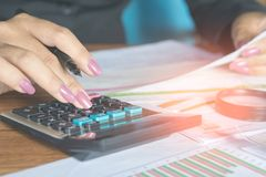Business woman hand calculating her monthly expenses during tax season. With some bills on desk Stock Image