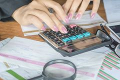 Business woman hand calculating her monthly expenses during tax season with some bills Stock Photos