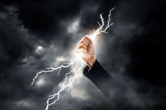 Business woman hand clenching lightning flash. Concept background royalty free stock image