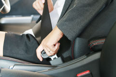 Business woman hand fastening a seat belt. Royalty Free Stock Photos