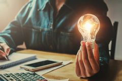 business woman hand holding light bulb in office. conept saving royalty free stock photos