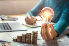 business woman hand holding lightbulb with coins stack on desk. concept saving energy royalty free stock photo