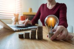 Business woman hand holding lightbulb with coins stack on desk. stock photos