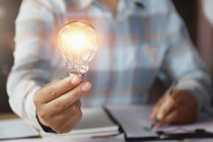 business woman hand holding lightbulb in office. concept saving energy royalty free stock image