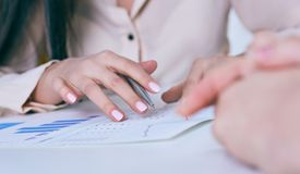Business woman hand holding pen and pointing at financial diagram, graph during conference sitting at the office desk. stock image