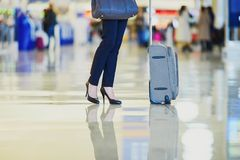 Business woman with hand luggage in an airport Stock Photo
