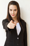Business woman hand pointing forward with friendly smile. Woman in business suit hand pointing forward with friendly smiling face expression Royalty Free Stock Photography