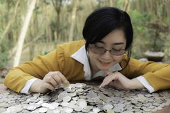 Business woman Hand Protecting With Stacked lots Coin, Portrait of beautiful happy young lady hands Pick up money on wooden table royalty free stock photos