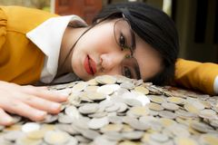 Business woman Hand Protecting With Stacked lots Coin, Portrait of beautiful happy young lady hands Pick up money on wooden table stock photos