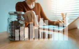 Businesswoman hand puting coins in glass for saving money. royalty free stock image