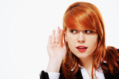 Business woman with hand to ear listening isolated Stock Image