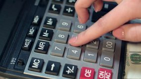Business woman hand using calculator at office. Calculator on dollar banknotes. Business woman hand using calculator at office. Close up of financial adviser stock footage