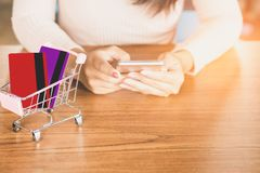 Business woman hand using smart phone to order online pay by credit card. In shopping cart model on desk Royalty Free Stock Photo