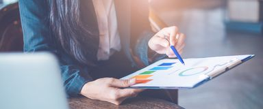 Business woman hand work on charts and graphs that show results.She uses the pen to point to the graph.Web banner royalty free stock image