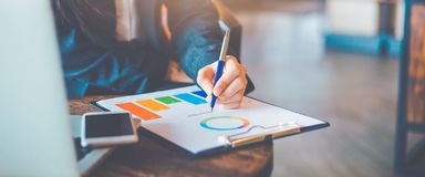 Business woman hand work on charts and graphs that show results.She uses the pen to point to the graph.Web banner royalty free stock images
