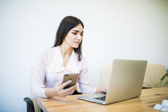 Business woman hand working and smart phone and laptop and graph business with social network diagramon office desk in office with Stock Photo