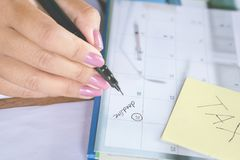 Business woman hand writing on calendar deadline word Royalty Free Stock Image
