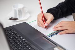 Business woman hand is writing on a notepad with a pencil. compu Stock Photos