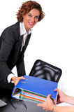 Business Woman Handing Over a Binder. A business woman, sitting on her desk, handing a large blue binder to an associate's hands Royalty Free Stock Images