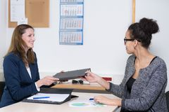 Business woman is handing over a file to another woman Royalty Free Stock Photos