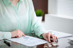 Business woman hands in a green blouse sitting at the desk in the office and examine the financial results , the right Stock Photo