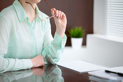 Business woman hands in a green blouse sitting at the desk in the office and holding glasses, the right window . She is Stock Photography