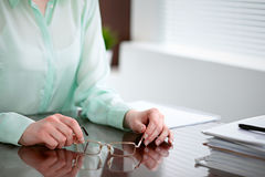 Business woman hands in a green blouse sitting at the desk in the office and holding glasses, the right window . She is Royalty Free Stock Photography