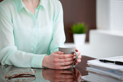 Business woman hands  in a green blouse sitting at the desk in the office and is holding a gray cup, right window. She is  thinking about  business problems Royalty Free Stock Photography