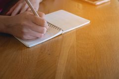 Business woman hands with pencil writing on notebook. Desk of brown stock images