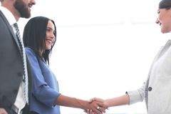 Business woman handshaking with an other person. Businesswomen Shaking Hands In Modern Office stock photography