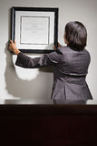 Business woman hanging framed certificate. Business women hanging framed certificate royalty free stock image