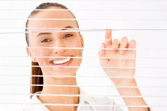 Business woman. Happy business woman peeking through a venetian blind in an office Royalty Free Stock Image