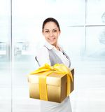Business woman happy smile hold golden gift box. In hands. Businesswoman in modern office Royalty Free Stock Photography