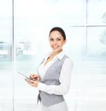 Business woman happy smile hold tablet pad. Computer empty touch screen with copy space, young businesswoman wear vest smiling in modern office Stock Photography