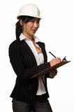 Business woman in hard hat. Asian woman in business suit wearing a white safety hard hat holding and writing on a chart royalty free stock image