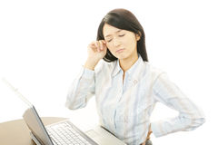 Business woman having a headache. Asian business woman sitting at desk working on laptop Royalty Free Stock Images
