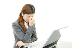 Business woman having a headache. Asian business woman sitting at desk working on laptop Royalty Free Stock Photos
