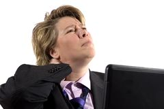 Business woman having neck trouble. A business woman grabbing her neck in pain. She's worked to long and the laptop stock images