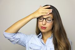 Business woman with a headache holding her head on gray background stock photography
