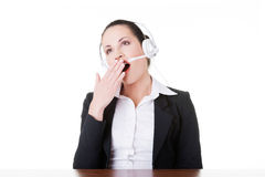 Business woman with headphones yawning. Royalty Free Stock Photography