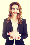 Business woman with headset holding piggy bank Stock Photo