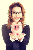 Business woman with headset holding piggy bank Royalty Free Stock Images