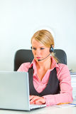Business woman with headset working on laptop Stock Photos