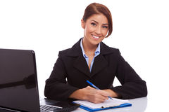 Business woman at her desk writing Stock Photography