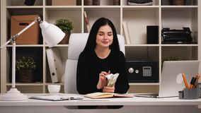 Businesswoman at office. Counting money and looking at camera. Happy. stock video footage