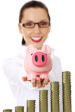 Business woman with her savings in a piggy bank Stock Images