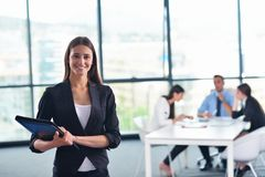 Business woman with her staff in background at office Stock Photos