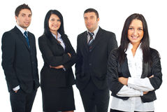Business woman and her team. Business woman standing in front of camera with hands crossed and her team smiling in background Stock Images