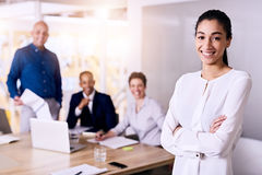 Business woman and her team all looking at camera smiling. Young confident business women standing in front of her business colleagues as all of them look happy Stock Photos